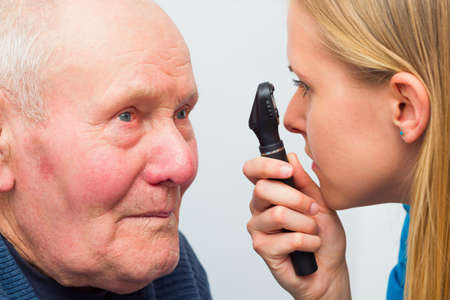 eye test: Optician consulting elderly patient with cataracts and other eye problems.