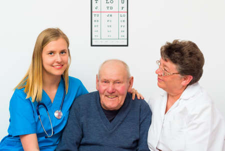 medical attendance: Happy elderly man being supported by his doctor and nurse. Stock Photo