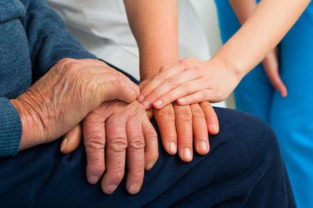 an elderly person: Apoyando las manos por el sufrimiento de edad avanzada con demencia. Foto de archivo