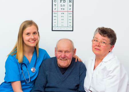 the elderly caregivers: Happy elderly man at the nursing home with his caregivers. Stock Photo