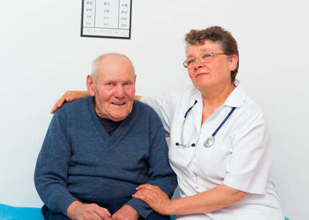 medical attendance: Cheerful middle-aged doctor and happy elderly patient at the nursing home. Stock Photo