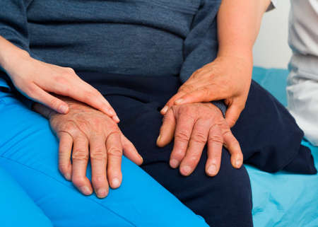 Caring hands of a nurse and doctor for elderly patient with Parkinsons disease. Stock Photo