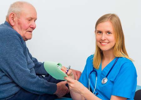approfondi: Jeune m�decin �crit sur ordonnance pour les patients �g�s apr�s un examen m�dical approfondi.