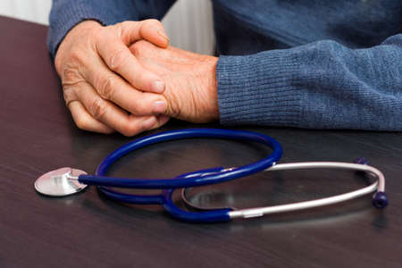 health care concept: Elderly health care concept - old hands  laying near a stethoscope.