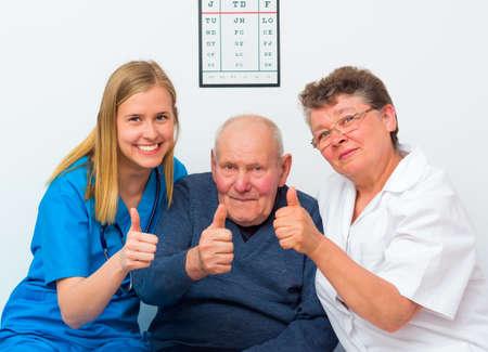 ancianos felices: Momentos felices en el hogar de ancianos, hombre mayor que muestra los pulgares para arriba con sus cuidadores. Foto de archivo