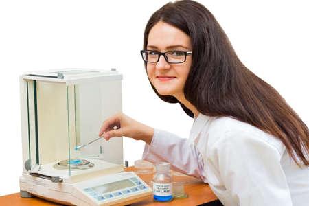 balanza de laboratorio: Analista químico joven que trabaja en el laboratorio, de medición en la escala.