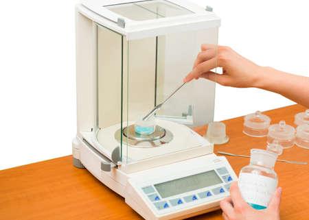 balanza de laboratorio: Farmacéutico que mide sustancia activa con la escala de análisis para la determinación de la dosis.