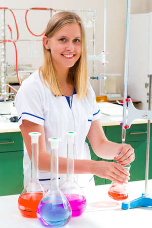 well equipped: Young scientist making acid base titration in well equipped laboratory.