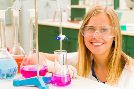 titration: Young blond woman researching at the chemistry college  in laboratory.