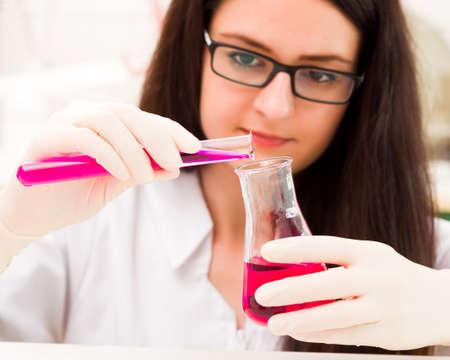 bureta: dulce estudiante joven que es ocupado con el análisis químico. Foto de archivo