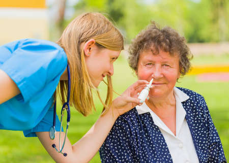 Family doctor maintaining senior woman patient with allergy and hayfever. Stock Photo