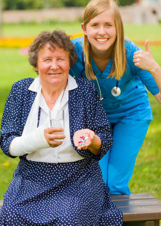 gypsum: Thumbs up from doctor for d vitamin and alternative medicine effective for injured elderly woman. Stock Photo