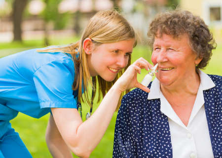 Family doctor: Kind family doctor spraying nose drop for senior woman with hayfever. Stock Photo
