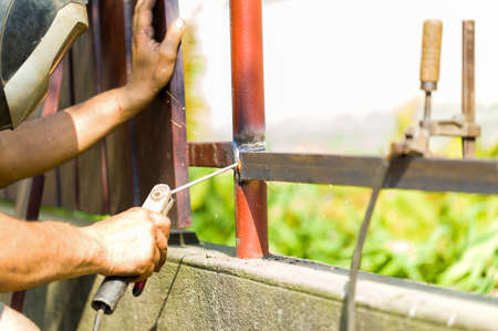 sparking: Closeup of sparking work of welding steel part of fence with protective workwear. Stock Photo