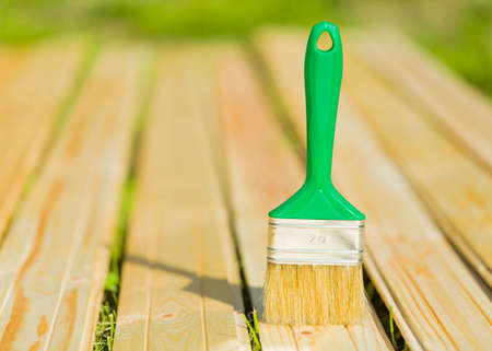 Readied paint brush to apply protective oil on boards parts of architecture. Stock Photo