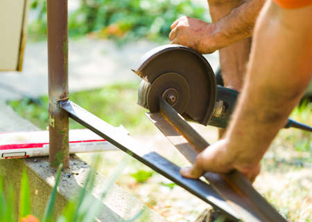 flex: Fence construction with flex angle grinder by male worker hand.