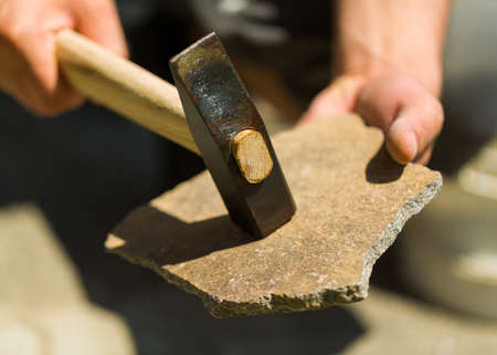 Male hands splitting with hammer rubble to obtain with it quarry stone.