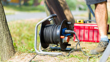 manufacturing equipment: Manufacturing equipment outdoors on the grass, extension cord and welder.