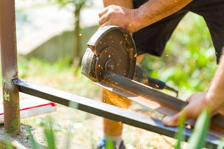 Mechanical work of man preparing steel part of fence. Stock Photo
