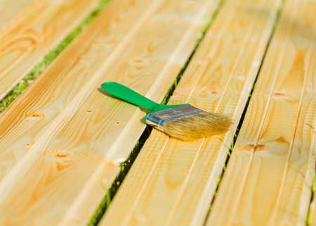 treated board: Closeup of brush on board prepared to apply dye on it.