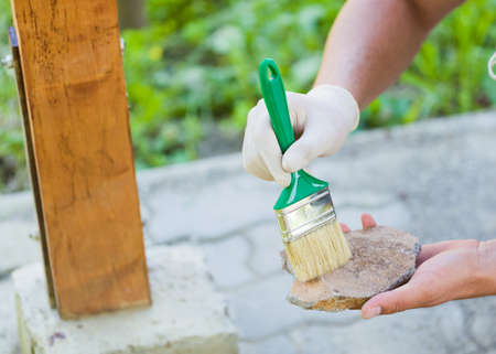obtain: Handyman with protective glove applying with putty knife broken stone to obtain refreshment of garden resting place. Stock Photo