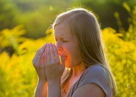 Attractive young woman sneezing because of asthmatic allergy in summer nature.