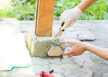 Male hand plastering splitted  stones with putty knife to get ornament.