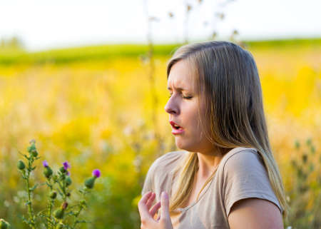 Blonde woman sneezing because of colza allergy on the flowery meadow.