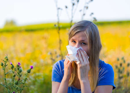 Allergiv woman using handkerchief on runny nose.