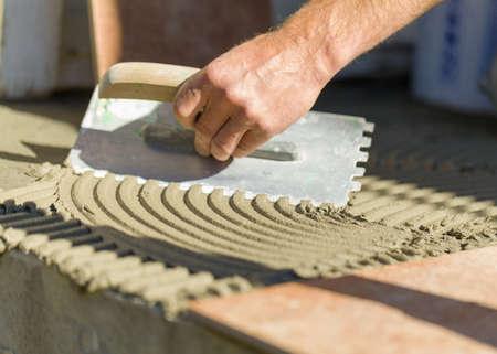 pegamento: Primer plano del hombre de la mano de obra del embaldosado con material adhesivo al aire libre en la puerta delantera.