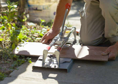 tile cutter: Laborer hand professional work with tile cutter in court to cut tiles.