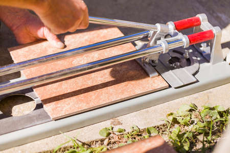 tile cutter: Closeup  of  bricolage work with tile cutter for home improvement. Stock Photo