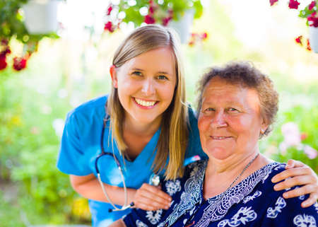 Smiling doctor with supporting hands and her happy senior woman patient at the nursing home.