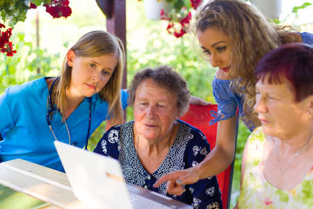 Director with nurse making elderly nursing home contract with pensioner women.