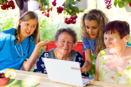 Young lady demonstrating with a laptop with elderly women next to another disgusted colleague. Stock Photo