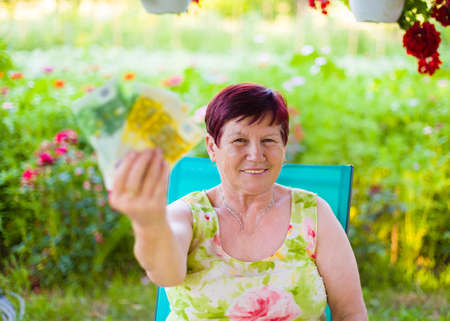 Portrait of proud pensioner woman holding her saved money. Stock Photo