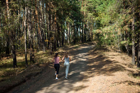 Two girls of the athlete perform a run in the morning in the sunny forest. Stok Fotoğraf