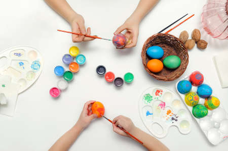 Joint traditional coloring of the symbol of Easter. Hands, brushes, paints, palette, eggs on a white background.