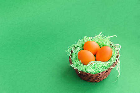 Three Easter eggs in a wicker basket on a green background.
