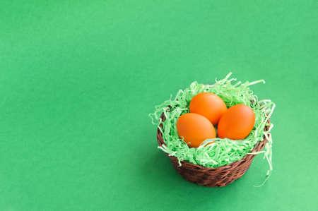 Three Easter eggs in a wicker basket on a green background. Stok Fotoğraf - 145653176