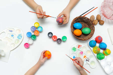Preparing for Easter. Children paint on eggs. View from above on a white background.