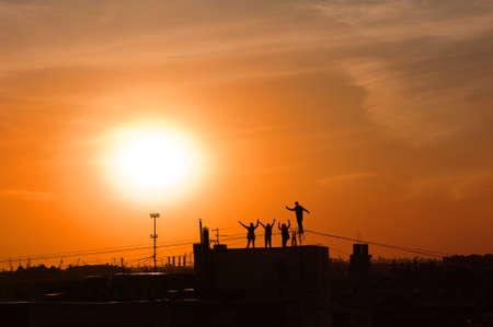 Silhouettes of young people dancing on the St. Petersburg roof against the background of an orange sunset. Stok Fotoğraf - 145682242