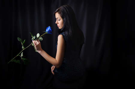 Girl with shadowy hair in a black dress looks at a blue rose, low key