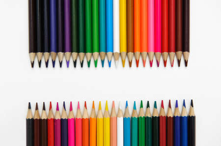 set of colored pencils arranged in a two rows horizontally opposite each other on a white background.