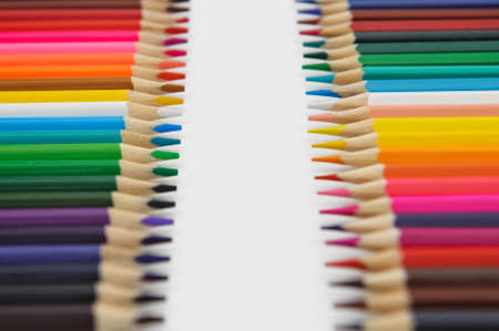 set of colored pencils arranged in a two rows vertically opposite each other on a white background. selective focus