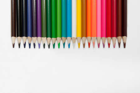set of colored pencils arranged in a row horizontally on a white background