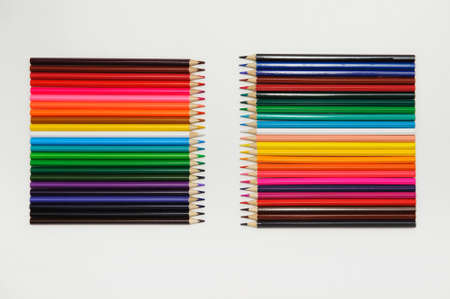 set of colored pencils arranged in a two rows vertically opposite each other on a white background
