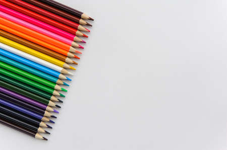 set of colored pencils arranged in a row horizontally on a white background. Stok Fotoğraf