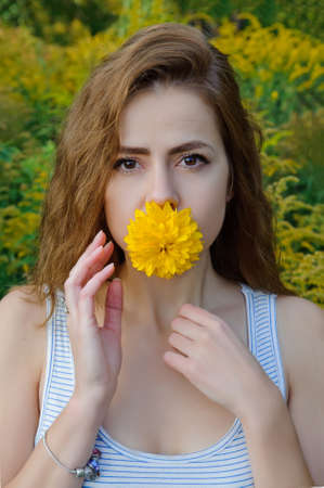 portrait of a caucasian girl with a yellow flower in her mouth Stok Fotoğraf