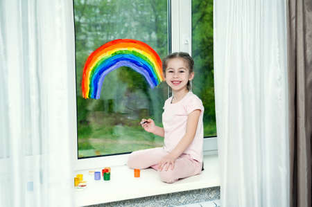 Little smiling girl sits by the window on the windowsill and draws a rainbow on the glass Stok Fotoğraf - 148797245